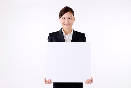 人物 日本人 女性 若い 若者  20代 スーツ 就職活動 就活 就活生  社会人 OL ビジネス 新社会人 新入社員  フレッシュマン 面接 真面目 清楚 屋内  白バック 白背景 上半身 ボード 白紙 持つ メッセージ 案内 説明 ビジネスマン mdjf007