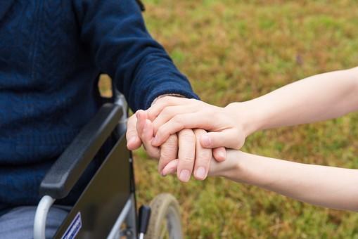 老人 高齢者 お年寄り シニア 男性 男 おとこ  2人 二人  介護士 看護師 エプロン  介護 不自由 椅子 ヘルパー 屋外 緑 木々 木 ジャケット ズボン 青  車いす 車椅子    座る  握る 手 両手  アップ 散歩 外出