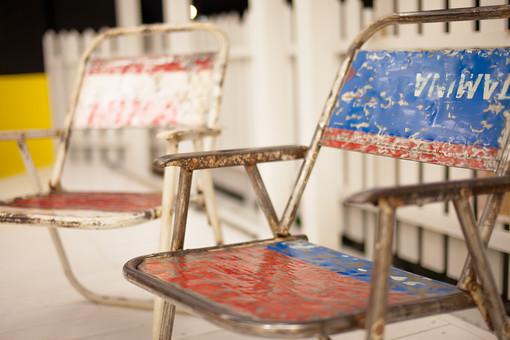椅子 パイプ椅子 ペイント ペンキ 質感 リメイク リサイクル 再利用 アンティーク 古びた 古い 剥げた 色あせた 使い込んだ インテリア フェンス 柵 青 赤 白 雑貨屋 雑貨店 インテリアショップ アンティークショップ 背景ボケ ボケ味