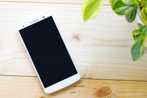 木材の上に置かれたスマートフォンの写真