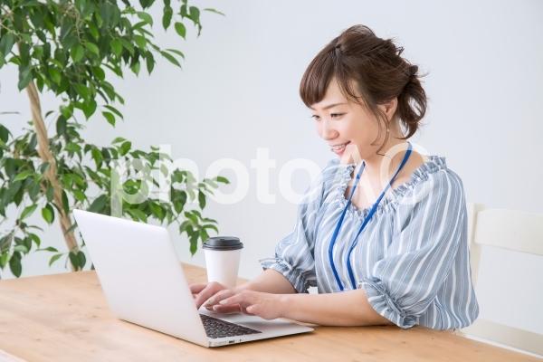 ノートパソコンで仕事をする女性(笑顔)の写真