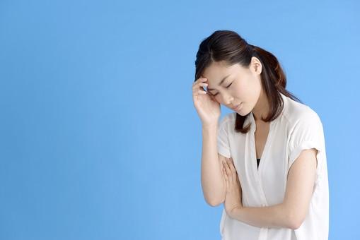 女性 ポーズ 人物 30代 日本人 黒髪 爽やか カジュアル 屋内 横向き ブルーバック 青背景 半そで 白  腕組 頭痛 悩み 苦痛 苦難 心配 辛い 頭 手をやる 目 瞑る mdjf013
