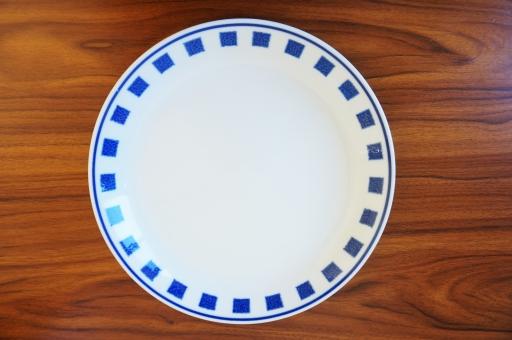 木目テーブルの上の白い皿(柄あり)の写真