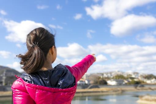青空に向かって指をさす女性の写真