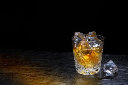 食品 飲料 ドリンク アルコール ウイスキー オンダロック ロック 洋酒 スコッチ 氷 夜のムード バーイメージ ムードのある 大人のムード 夜の雰囲気 ロックグラス バカラ 琥珀 琥珀の液体 室内 落ち着く 透明感 写り込み ポストカード コピースペース 待ち受け画面 背景 バックグランド