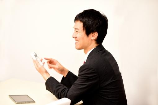 電卓で計算する社会人の男性の写真