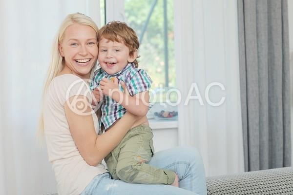 窓際にて息子を抱き寄せる母親2の写真