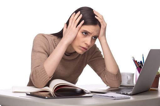 屋内 人物 外国人 女性 1人  大人 20代 30代  セーター 茶色 机 PC ノートパソコン タブレット パソコン   仕事 学習 勉強 趣味 ビジネス  ビジネスウーマン 若い 座る 頭を抱える 両手 頭 表情 放心 失敗 不安 ストレス 絶望 もうだめ やっちゃった どうしよう オーマイゴッド まさか 苦悩 頭痛 痛み 女 人 室内 白バック 白背景 mdff127