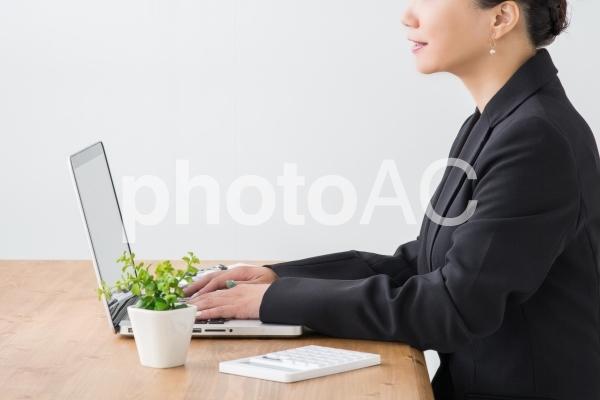 笑顔で考えるビジネスウーマンの写真