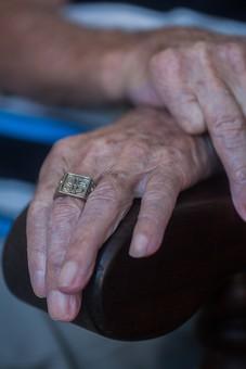 人物 老人 お年寄り 高齢者 シルバー  年老いた手 ハンドパーツ 手 指 ハンド  パーツ 手の表情 年老いた手 皺 しわ  シワ クローズアップ  椅子 イス いす 肘掛け ひじ掛け もたれる 寄りかかる 両手 指輪 正面 手元 手先 指先