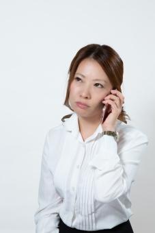 不機嫌にスマホで会話する女性2の写真