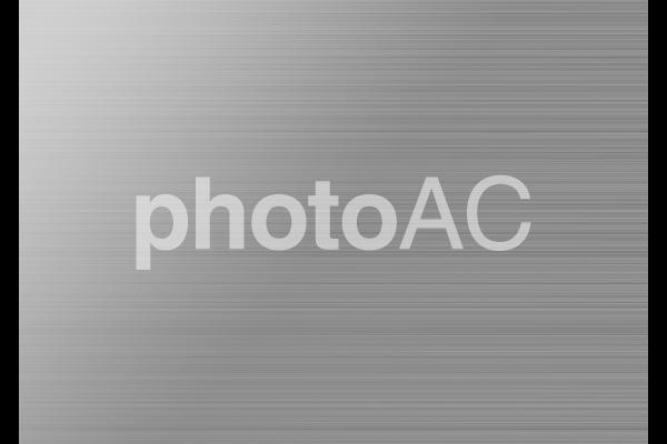 シルバー金属のヘアラインテクスチャ背景素材の写真