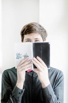 本 ブック 書物 書籍 図書 読書 読む 趣味 勉強 人物 男性 男 外国人 若い 若者 髭 20代 上半身 ページ 捲る めくる 開く 接写 クローズアップ アップ 顔 隠す チラリ ニヤニヤ にやける 笑う 笑顔 スマイル mdfm079