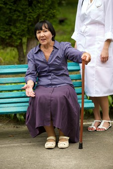 屋外 野外 外 病院 庭 公園 ベンチ 外国人 老人 高齢者 女性 おばあさん おばあちゃん 患者 女医 白人 金髪 白衣 医師 医者 スカート 座る 杖 つえ 突く つく 持つ 立つ mdfs016