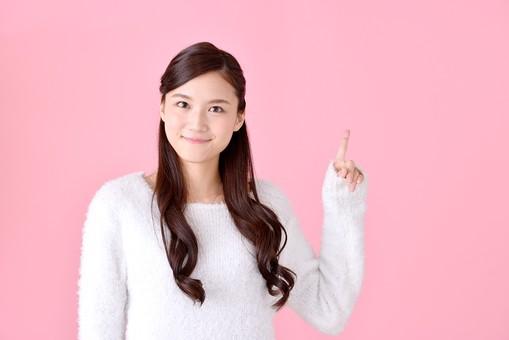 人物 女性 日本人 若者 若い  20代 美人 かわいい ロングヘア カジュアル  ラフ 私服 セーター ニット 屋内  スタジオ撮影 背景 ピンク ピンクバック ポーズ  おすすめ 指差し 指さす 上 注目 説明 案内 アドバイス 笑顔 mdjf007