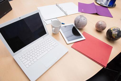 全面 ノートパソコン ラップトップ パソコン マグカップ タブレット iPad ファイル 地球儀 デスク 机 スピーカー 水 ミネラルウォーター 白 白色 赤 赤色 紫 紫色 ボールペン デスクトップ 散らかっている 屋内 室内 会社 ビジネス 仕事 職場 仕事場 働く オフィス