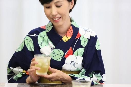 浴衣を着て冷たいお茶を飲む女性の写真