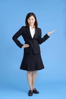 人物 女性 日本人 20代 若者  ビジネス スーツ 黒 紺色 セミロング  OL 社会人 会社員 ビジネスマン 就活  就職活動 真面目 ポーズ 屋内 スタジオ撮影  ブルーバック 案内 説明 誘導 おすすめ 全身 mdjf013