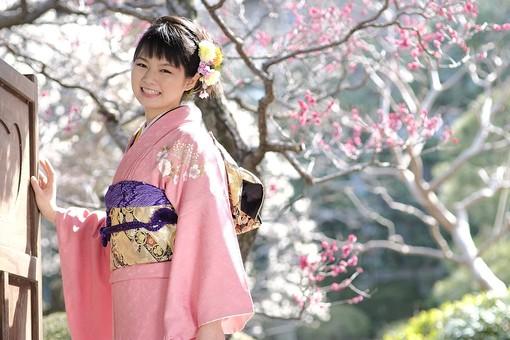 日本人 女性 20代 和服 着物 伝統 文化 衣装 晴れ着 振袖 成人式 卒業式 結婚式 正装 礼装 華やか 髪飾り ピンク 屋外 外 庭 緑 樹木 花 春 梅 上半身 笑顔 日差し 陽射し お見合い 振り袖 正月 mdjf023
