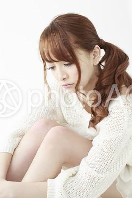 膝を抱えてぼんやりする女性6の写真