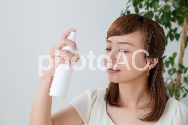 ミスト化粧水をかける女性の写真