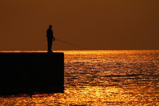 釣り 磯釣り 釣り人 海釣り 夕日 1人 釣竿 海 日本 太陽 オレンジ色 立つ 夕方 シルエット 水平線 岬 夕焼け 反射 光 つり 輝く 輝き 波 金色 男性