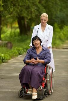 屋外 野外 外 病院 庭 公園 外国人 老人 高齢者 女性 おばあさん おばあちゃん 患者 女医 白人 金髪 白衣 医師 医者 スカート 車椅子 車いす 乗る 座る 押す 散歩 歩く 立ち止まる 止まる カメラ目線 mdff142 mdfs016