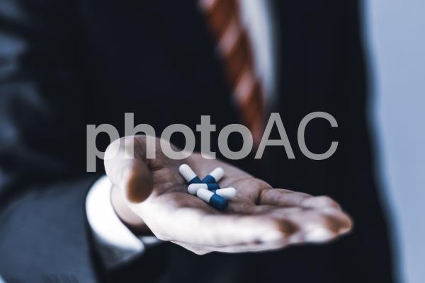 薬を服用するビジネスマンの写真
