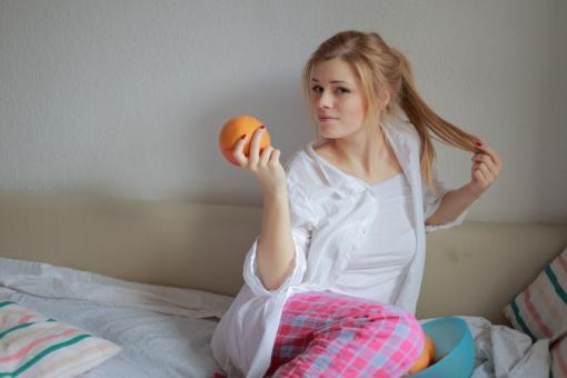 リラックス プライベート 外国人 女性 女 20代 白人 ブロンド ブロンドヘヤ 金髪 ロングヘア パジャマ ルームウェア 部屋着 自室 部屋 休日 休み まったり 全身 ベッド 布団 チェック ひとり 寝起き 朝食 朝ごはん グレープフルーツ みかん 柑橘 カメラ目線 髪を触る ポニーテール mdff010