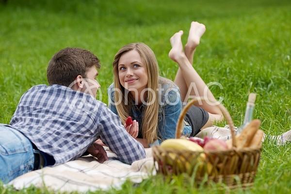 寝そべってイチゴを食べるカップル9の写真