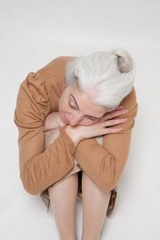 人物 女性 外国人 外人 外国人女性  外人女性 高齢者 老人 年配 シニア  シルバー モデル 60代 70代 白髪  ポーズ 屋内 スタジオ撮影 白バック 白背景 座る 体育座り 膝を抱える 考える 悩む ぼんやり 落ち込む 塞ぎこむ 俯瞰 mdfs004