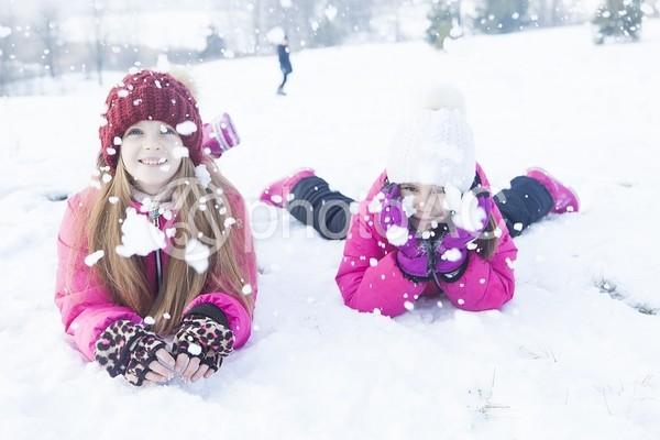 雪の上に寝転ぶ姉妹1の写真