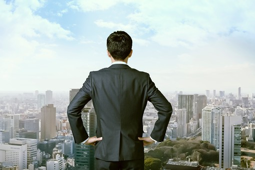 都会の風景とスーツの男性の後ろ姿2の写真