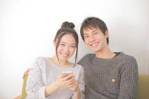 人物 男性 男子 女性 女子 若い 着席 デート カップル アベック 夫婦 新婚 白バック 白背景 部屋 リビング くつろぐ リラックス 仲良し 携帯 携帯電話 スマホ モバイル 情報 日本人 mdjm008 mdjf026