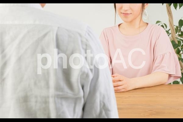 テーブルで話す男女の写真