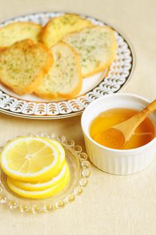 パン トースト バケット フランスパン ガーリックトースト パセリ レモン スライスレモン 蜂蜜 はちみつ ハチミツ 小皿 ガラス スプーン 皿 食事 朝食 夕食 洋食 食べ物 焼きたて 輪切り 食卓 レストラン