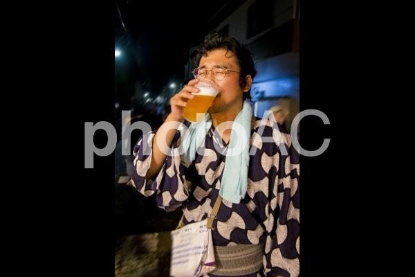 お祭りで生ビールを飲むエガちゃんの写真