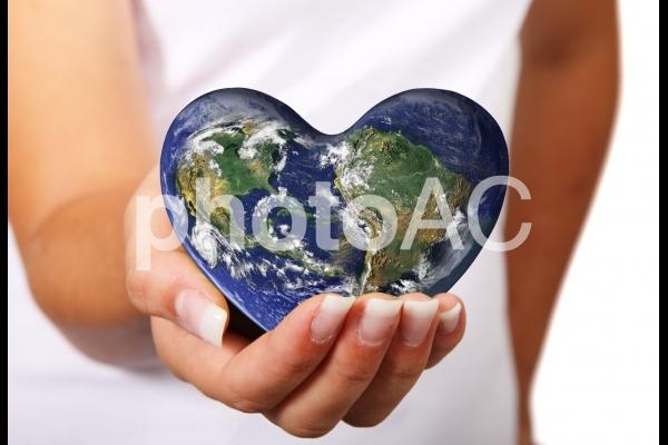 ハートの地球を持つ女の子包む手の写真