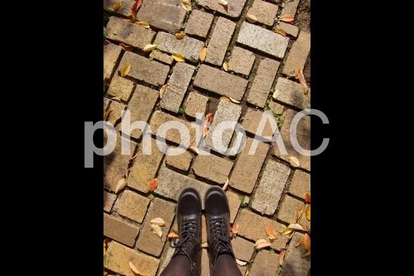 レンガの小道に立つ女性の写真