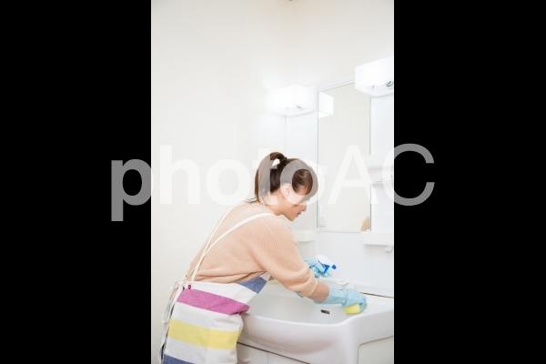 洗面台を掃除する女性(シンク)の写真