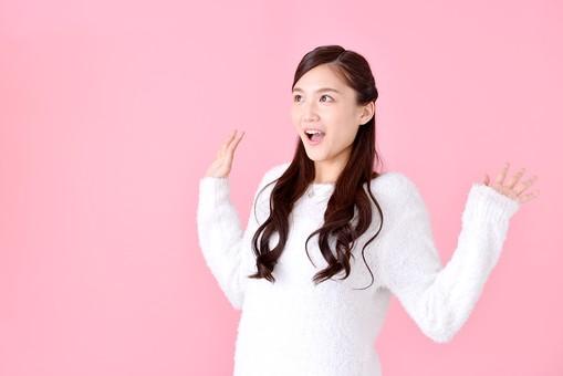 人物 女性 日本人 若者 若い  20代 美人 かわいい ロングヘア カジュアル  ラフ 私服 セーター ニット 屋内  スタジオ撮影 背景 ピンク ピンクバック ポーズ  おすすめ 上半身 驚く びっくり ビックリ 手を広げる オーバーリアクション うれしい 嬉しい サプライズ mdjf007