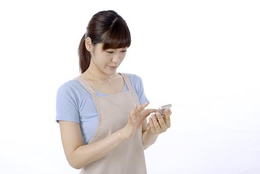 人物 屋内 白バック 白背景 日本人 1人 女性 20代 30代 エプロン  奥さん 奥様 婦人 家庭人 夫人 主婦 若い 表情 笑顔 微笑む 携帯電話 携帯 電話 スマホ スマートフォン タップ スワイプ タッチ 画面 見る 下を向く うつむく 指 手 持つ mdjf018
