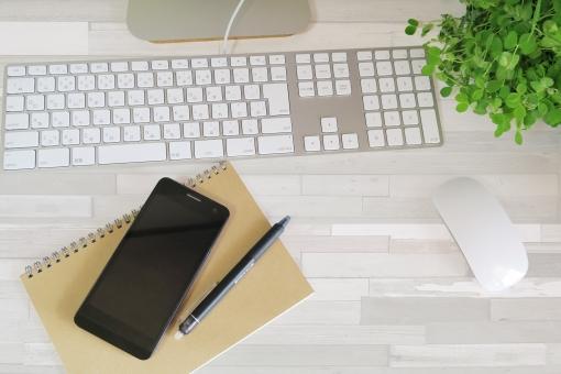 パソコンとスマートフォンの仕事場-白い木目デスクの写真