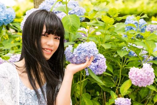笑顔でアジサイに触れる夏の女性の写真