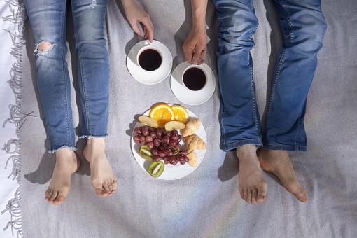 ベッドで横になるカップルの足1の写真