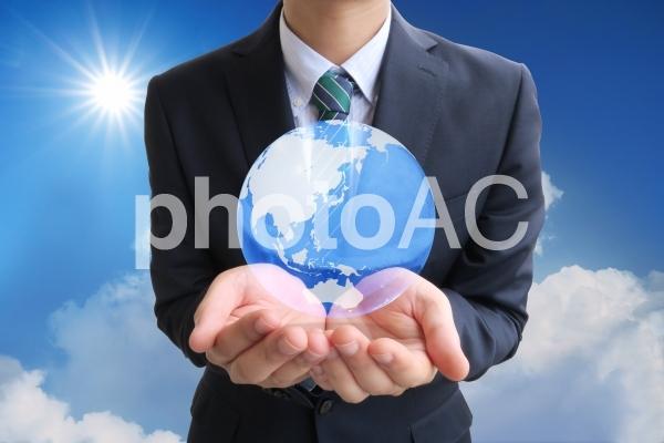 地球を手の平に乗せるビジネスマンと夏の太陽と青空の写真