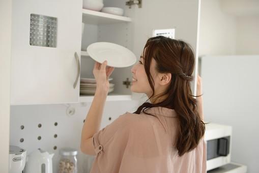 日本人 女性 女 30代 アラサー ライフスタイル 部屋 室内 ポーズ ピンクベージュ ピンク チュニック  カジュアル プライベート 部屋着 私服  キッチン  主婦  ハーフアップ 食器 食器棚 後片付け 片づけ お片付け 後姿 背中 背面 皿 取り出す 直す 戻す mdjf013