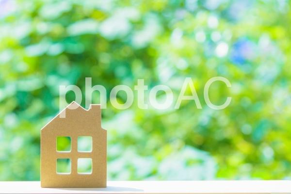 緑ぼかし背景と木製の住宅模型の写真