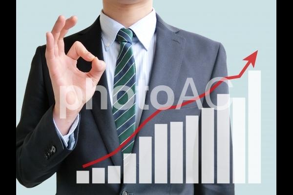 ビジネスマンと業績アップのグラフ-青背景の写真