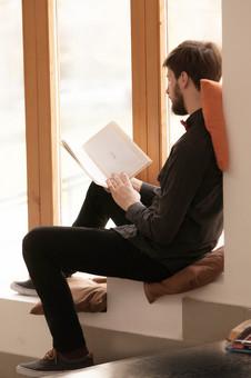 本 ブック 書物 書籍 図書 読書 読む 趣味 勉強 人物 男性 男 外国人 若い 若者 髭 20代 全身 ページ 捲る めくる 開く 座る 接写 クローズアップ 横顔 クッション 窓際 窓辺 段差 段々 もたれる 寄りかかる mdfm079